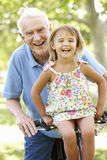 Senior man riding bike with granddaughter Royalty Free Stock Image