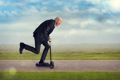 Senior man riding a scooter stock images
