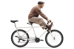 Senior man riding a tandem bicycle with legs up royalty free stock photo