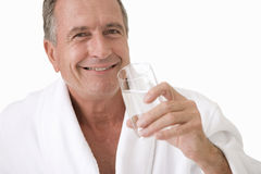 Senior man in robe holding glass of water, cut out Royalty Free Stock Images