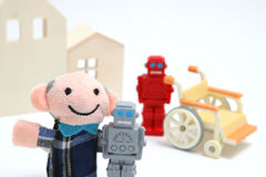 Senior man and robots with wheelchair on white background. Nursing care and robot assistant concept. Stock Photos
