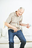 Senior man rocking with air guitar crutches Royalty Free Stock Photography