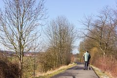 Senior man with rollator on a bikeway and sunny winter day. With blue sky in south germany Stock Photo