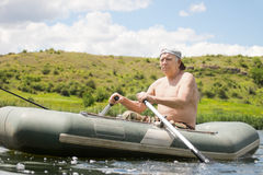 Senior man rowing an inflatable dinghy on a lake Stock Photo