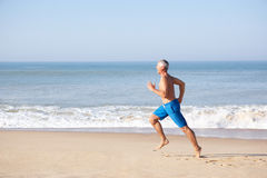 Senior man running on beach Stock Photo