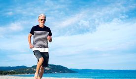 Senior man running on the beach. Healthy lifestyle exercise male seaside workout gray hair summer water runner jogging jogger speed sand exercising active fit stock photos