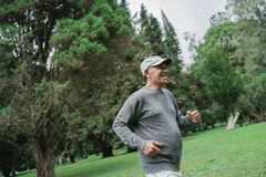 Senior man running in the garden. And exercising stock photo