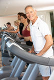 Senior Man On Running Machine In Gym. Smiling at camera Royalty Free Stock Images