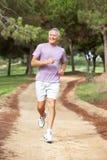 Senior man running in park royalty free stock images