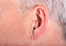 Senior man's ear with hearing aid. Close-up of a senior man's ear wearing a small hearing aid Stock Photo