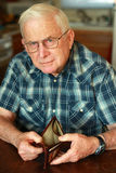 Senior man's empty wallet. An elderly man holds his wallet open showing there is no money. He has white hair, glasses, wears a watch, and is sitting in a kitchen Royalty Free Stock Photo