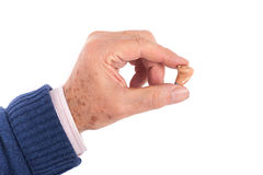 Senior man's hand showing a small hearing aid. Close up of a senior man's hand showing a CIC (Completely In Canal) hearing aid between his fingers. Studio shot stock photo