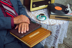 Senior man's hand touching an old photo album. Royalty Free Stock Image