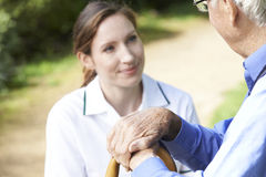 Senior Man's Hands Resting On Walking Stick With Care Worker In Royalty Free Stock Image