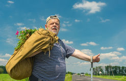 Senior man with sack and bunch of wild flowers Stock Image