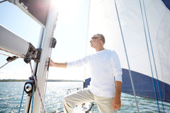 Senior man on sail boat or yacht sailing in sea. Sailing, age, tourism, travel and people concept - senior man on sail boat or yacht floating in sea stock photos