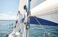 Senior man on sail boat or yacht sailing in sea. Sailing, age, tourism, travel and people concept - happy senior man on sail boat or yacht floating in sea royalty free stock image