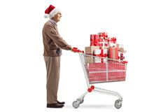 Senior man with a santa claus hat and a shopping cart with christmas presents. Full length profile shot of a senior man with a santa claus hat and a shopping stock photography