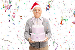 Senior man with Santa hat holding a cake Royalty Free Stock Photo