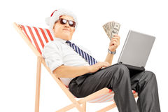 Senior man with santa hat seated on a chair holding banknotes Royalty Free Stock Photos