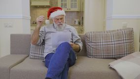 Senior man in Santa`s hat reads family wish list on Christmas stock footage