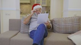 Elderly man in Santa`s hat reads wish list on sofa at home stock footage