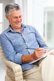 Senior man sat sketching Royalty Free Stock Photography