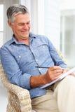 Senior man sat sketching. Smiling senior man sat sketching outside Royalty Free Stock Photography