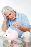 Senior man saving money in piggy. Worried senior man saving Euro money in piggy bank Stock Photo