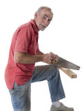 Senior man sawing wood. Senior man sawing a piece of wood for carpentry project. Over white stock photography