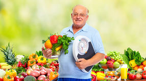 Senior man with scales and vegetables. Stock Images