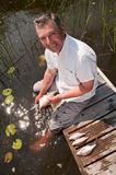 Senior man scaling fish Stock Photography