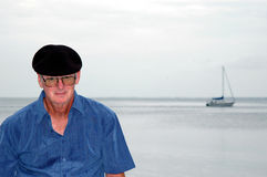 Senior man by the Sea. Portrait of a senior man by the ocean with sail boat in background royalty free stock image