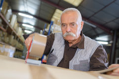 Senior man sealing cardboard box with tape dispenser. Senior man sealing cardboard box with a tape dispenser Royalty Free Stock Images