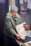 Senior man seasoning pork. An old man seasoning a large piece of pork and preparing it for the oven Royalty Free Stock Image