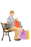 Senior man seated on a bench holding bags and typing a sms Royalty Free Stock Images