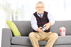 Senior man seated on a sofa playing video games at home Stock Photography