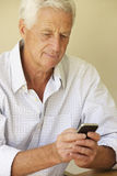 Senior Man Sending Text Message Sitting On Sofa Stock Images