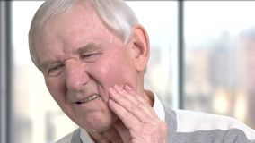 Senior man with sensitive tooth ache. Close up caucasian pensioner suffering from strong toothache, blurred background. Dental care concept stock video footage