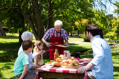 Senior man serving barbeque to family in park. Senior men serving barbeque to family in park on a sunny day Royalty Free Stock Images