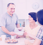 Senior man serving family lunch at home. Portrait of joyful smiling senior men helping to serve food during family lunch at home Royalty Free Stock Photography