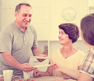 Senior man serving family lunch at home. Portrait of smiling senior men helping to serve food during family lunch at home Stock Images