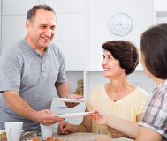 Senior man serving family lunch at home. Portrait of smiling senior men helping to serve food during family lunch at home Royalty Free Stock Photography