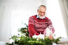 A senior man setting a table for a dinner at home at Christmas time. A happy senior man setting a table for a dinner at home at Christmas time stock photography