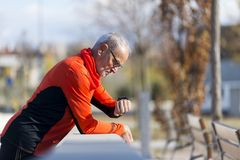 An Active jogging senior looking his smartwatch royalty free stock image