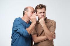Senior man sharing secret or whispering gossips into his son ear. Telling family secret concept. Senior men sharing secret or whispering gossips into his son ear royalty free stock photo