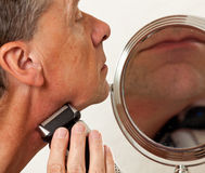Senior man shaving. Retired male shaving with electric razor in front of magnifying mirror royalty free stock photo