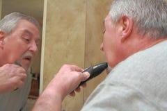 Senior man shaving. Baby bommer shaving in bathroom mirrow Royalty Free Stock Images