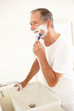 Senior Man Shaving In Bathroom Mirror. Smiling Stock Image