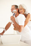 Senior Man Shaving In Bathroom With Wife Watching. Senior Man Shaving In Bathroom Mirror With Wife Watching Smiling Royalty Free Stock Photos